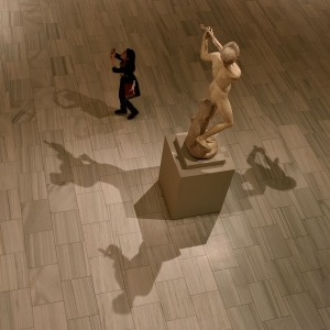 photo of the shadows of a statue and a museum visitor