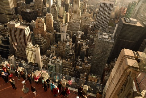 Tourists watching the buildings below on Top of the Rock at the Rockefeller Center.