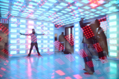 Double exposure photo of the room with motion activated lights. A tourist takes pictures. Top of the Rock at the Rockefeller Center.