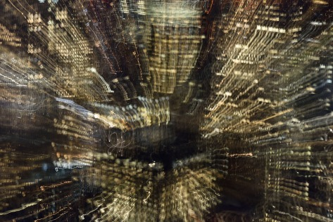 Long exposure photo with zooming and panning showing trails of city lights.