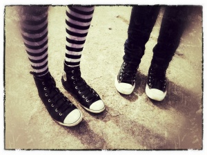 Photo of the legs from two young women wearing sneakers and striped leggings.
