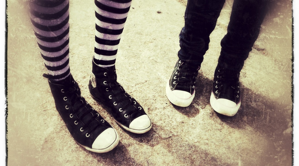 Photo of the legs of two young women wearing sneakers and striped leggings.