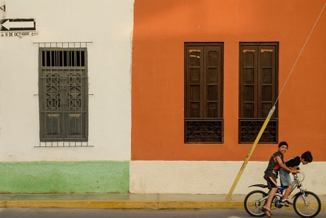 Photo of two boys in front of a colorful house in Lambayeque, Peru.