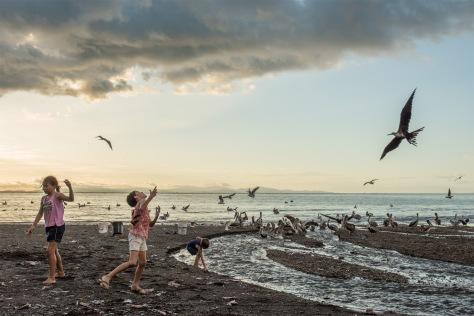 Corrected image of kids feeding fish scraps to seabirds in Tarcoles, Costa Rica.