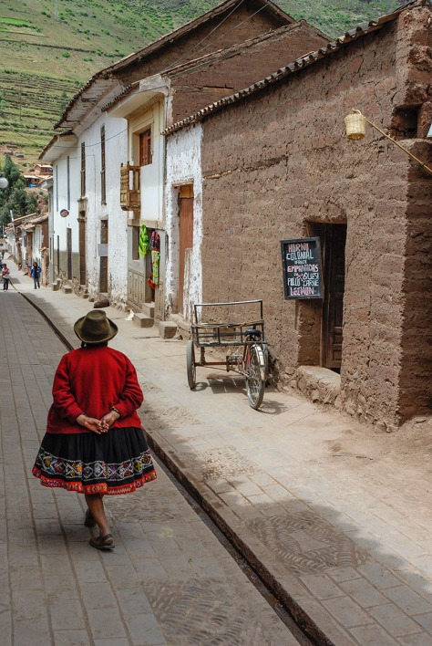 Photo of a woman walking in front of a bakery near Cuzco.