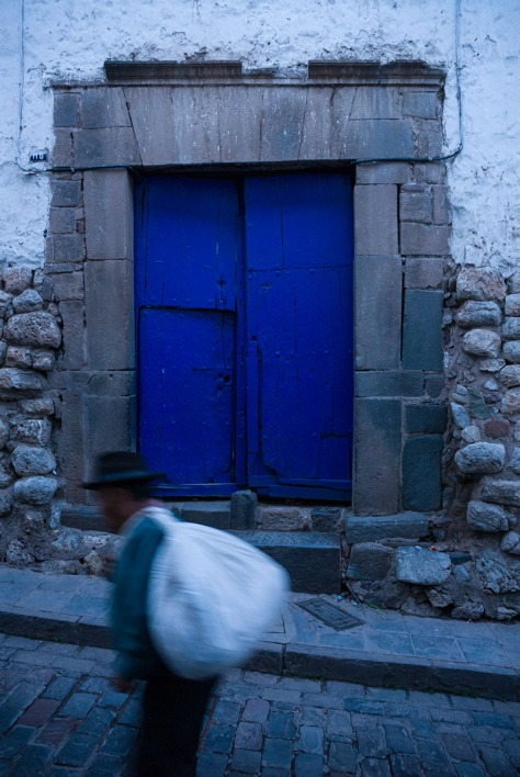 Photo of a man in front of a blue door in Cuzco.