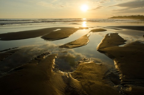 Photo of a sunset with sand pools very close to the camera showing hyperfocal focusing. Photo by Eduardo Libby