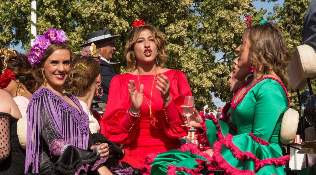 Image of three women wearing flamenco dresses while entering the Seville Fair on a horse carriage. Photo by Eduardo Libby