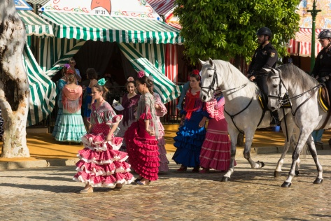 Young women and policemen on horseback at the Seville Fair
