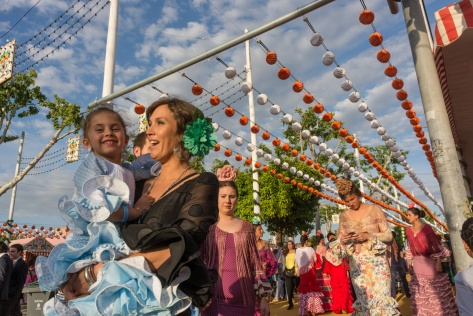 Image of woman carrying a child, both dressed with flamenco dresses at the Seville Fair. Photo by Eduardo Libby