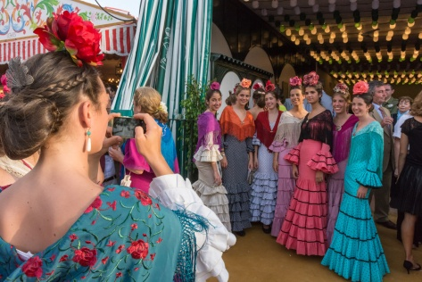 Image of a young woman taking a group picture at the Seville Fair. Photo by Eduardo Libby.