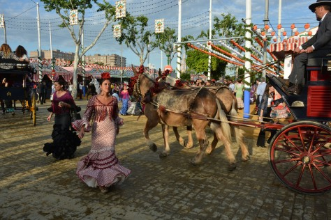 Image of young women in traditional dress and horse carriages at the Seville's Fair. Photo by Eduardo Lubby.