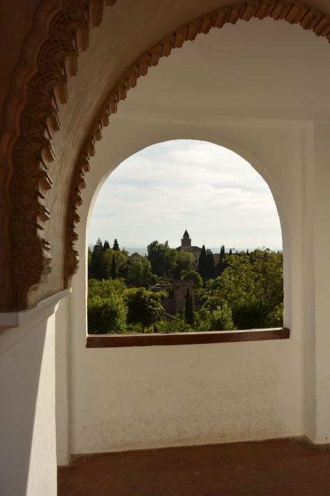 Garden view through an arched window of The Alhambra. Photo by Eduardo Libby