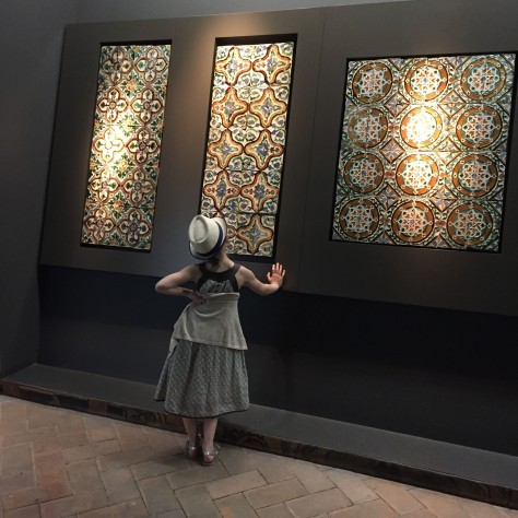 Image of a lovely-dressed young girl admiring classic tiles from Seville's Alcazar. Photo by Eduardo Libby.
