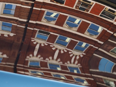 Reflection of a brick-building on a car. Photo by Eduardo Libby